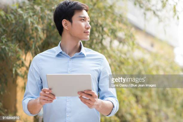 Young businessman holding a digital tablet outdoors