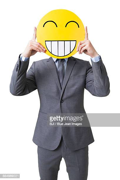 young businessman holding a happy emoticon face in front of his face - mask cartoon characters stock pictures, royalty-free photos & images