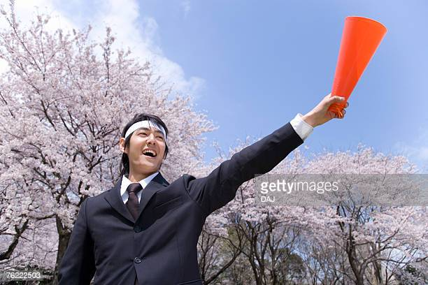 Young businessman holding a megaphone in the field of cherry blossoms, low angle view, Japan