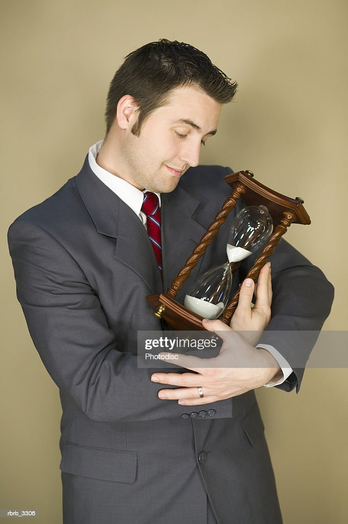 Young businessman holding an hourglass : Foto de stock