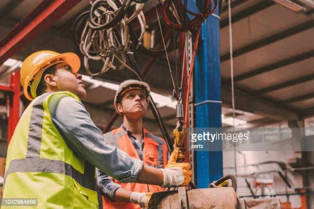 young businessman holding and working with remote control for operating crane - crane construction machinery stock pictures, royalty-free photos & images