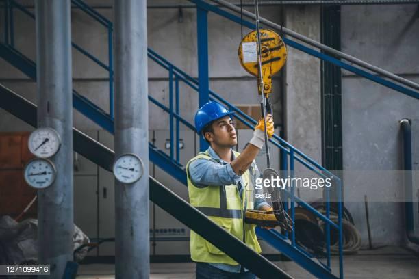 jovem empresário segurando e trabalhando com controle remoto para operar guindaste - indústria metalúrgica - fotografias e filmes do acervo