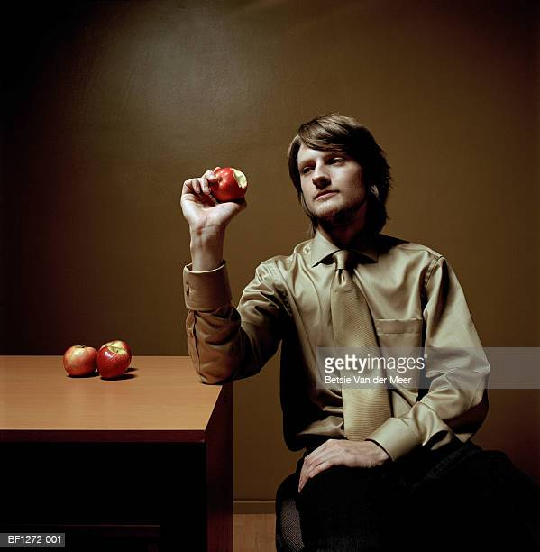 Young businessman holding apple, arm resting on desk, close-up