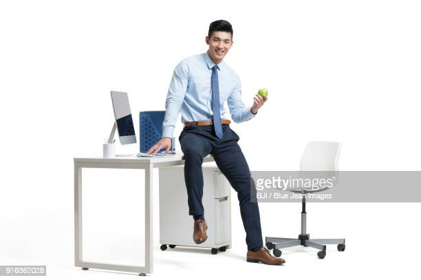 young businessman holding apple in office - shirt and tie stock pictures, royalty-free photos & images