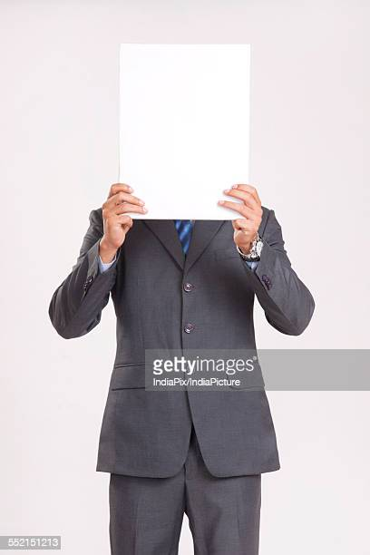 Young businessman holding blank placard in front of face over gray background