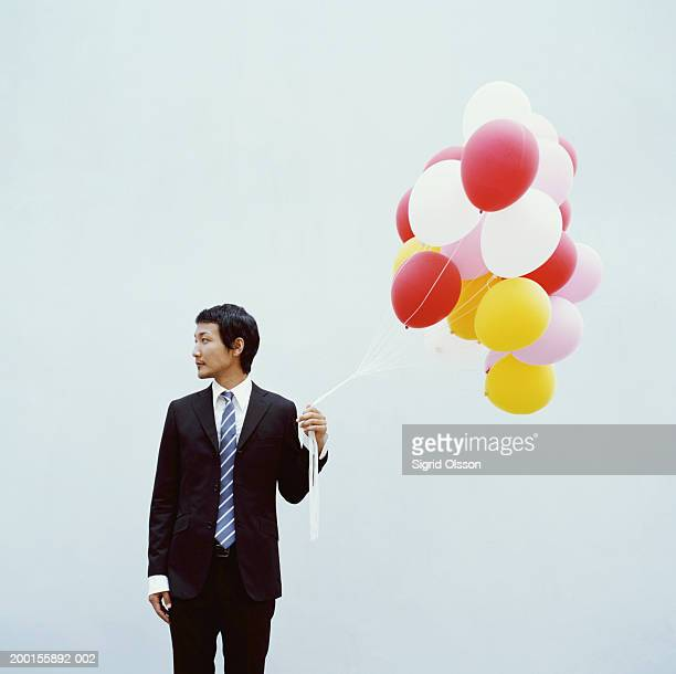 Young businessman holding bunch of balloons, looking away