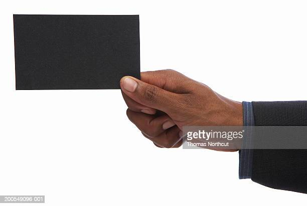 Young businessman holding business card, close-up of hand
