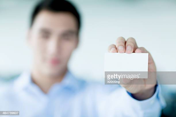 Young businessman holding business card to the camera