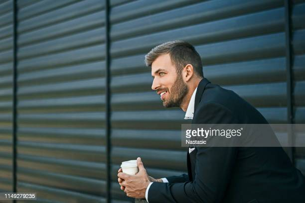 young businessman holding coffee to take away at early morning in front of office - one man only stock pictures, royalty-free photos & images