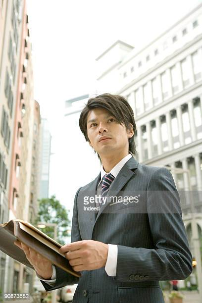 Young businessman holding diary in city