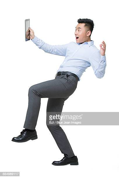Young businessman holding digital tablet with surprised expression