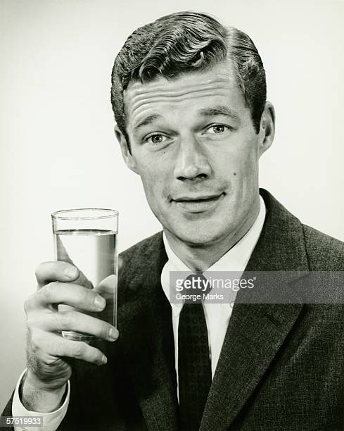 Young businessman holding glass of water, posing in studio, (B&W), portrait