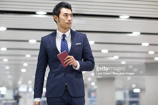 Young businessman holding passport in airport