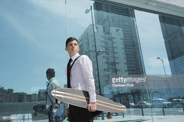 Young businessman holding skateboard against city