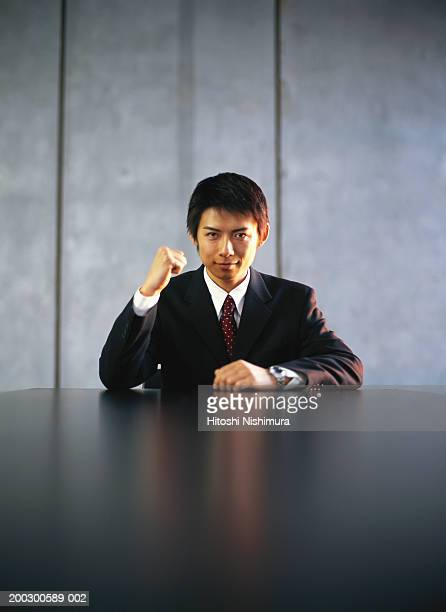 Young businessman holding up fist at office table, portrait