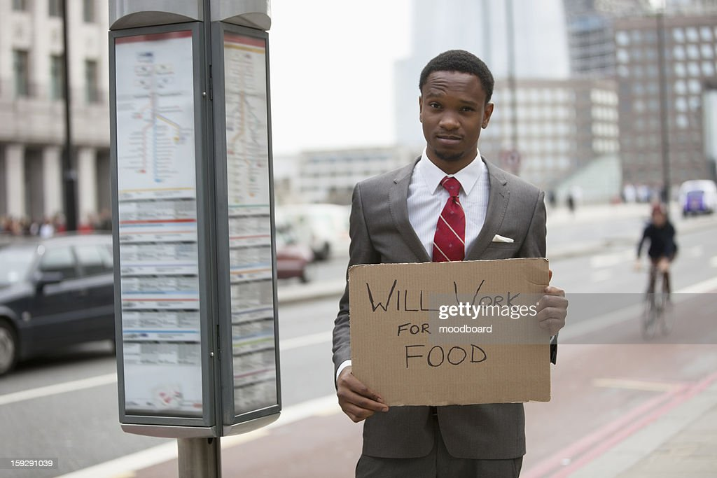 """Young businessman holding """"""""Will Work for Food"""""""" sign at street : Stock Photo"""