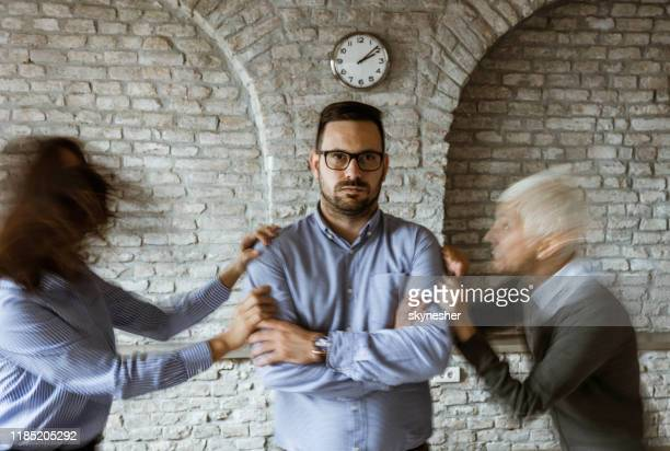 young businessman ignoring his colleagues who are fighting for him in blurred motion. - aggression stock pictures, royalty-free photos & images
