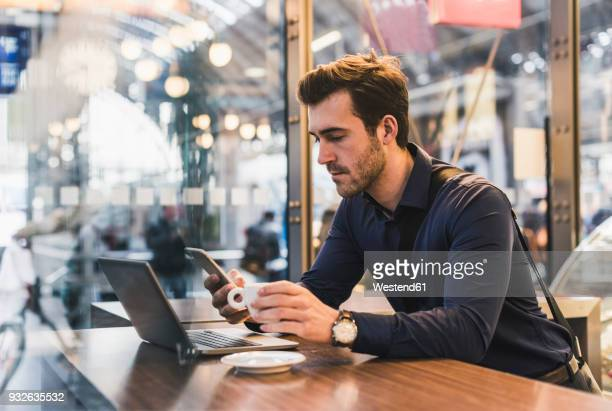 young businessman in a cafe at train station with cell phone and laptop - bahnhof stock-fotos und bilder