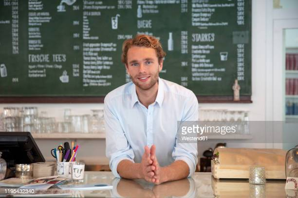 young businessman in a cafe, leaning on counter - gründer stock-fotos und bilder