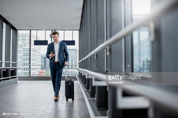 young businessman in a passageway with cell phone, earbuds and rolling suitcase on the go - geschäftsreise stock-fotos und bilder