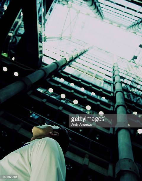 Young businessman in atrium of building, looking up, low angle view