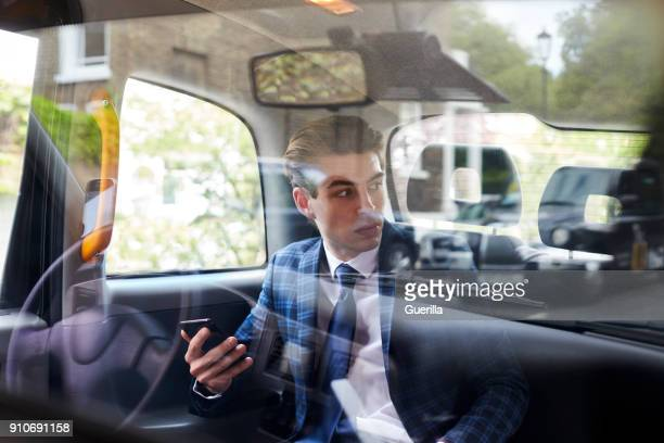 young businessman in back of london taxi, seen through glass - checked suit stock pictures, royalty-free photos & images