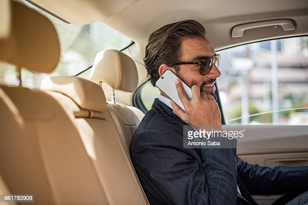 Young businessman in car backseat wearing sunglasses and talking on smartphone, Dubai, United Arab Emirates