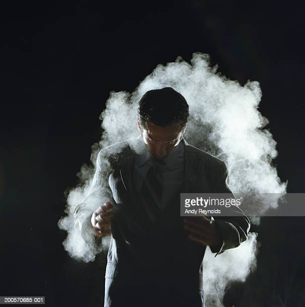 Young businessman in dust cloud, looking down