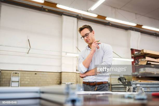 young businessman in factory working on plan - 袖を折った袖まくり ストックフォトと画像
