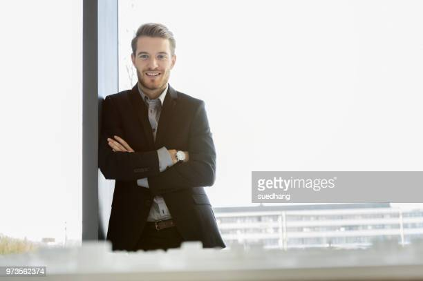young businessman in front of office window looking down at architectural model - frente fotografías e imágenes de stock