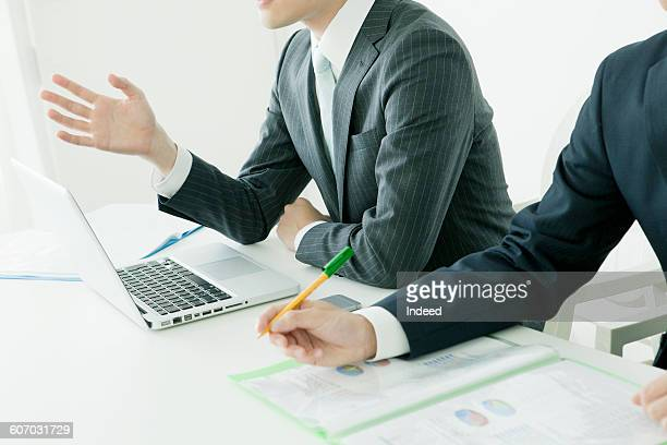Young businessman in meeting using laptop