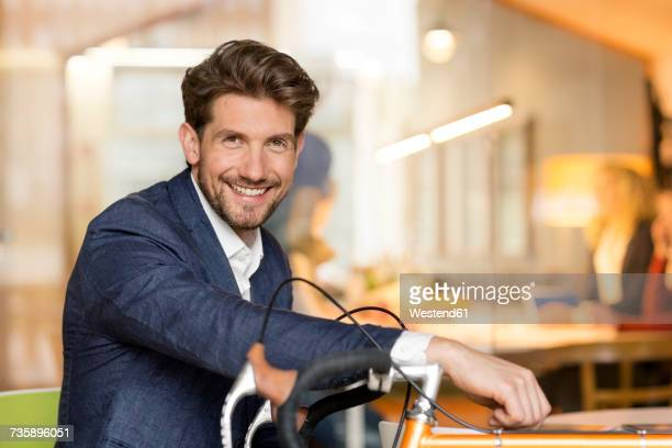 Young businessman in office leaning on his racing bike