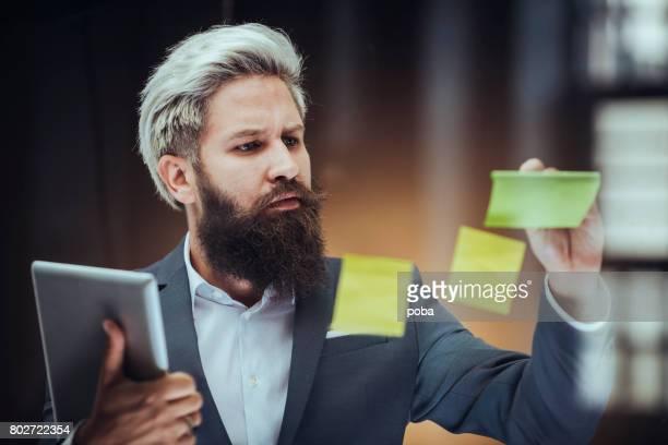Ung affärsman i office tittar på anteckningar