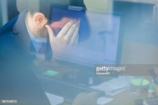 Young businessman in office with head in hand
