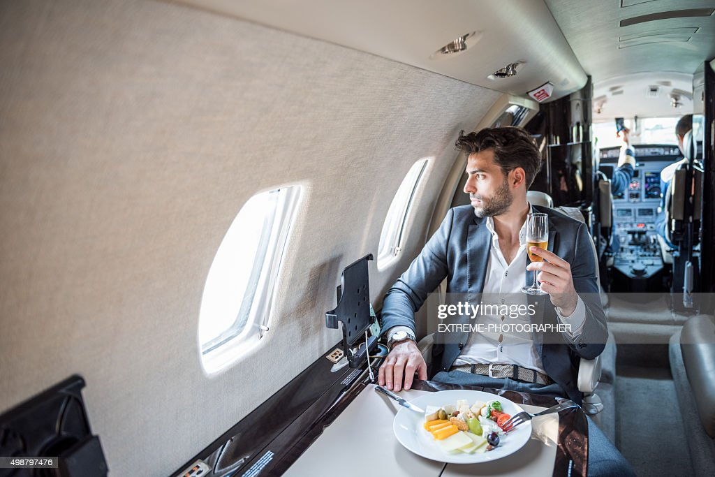 Young businessman in private jet airplane : Stock Photo
