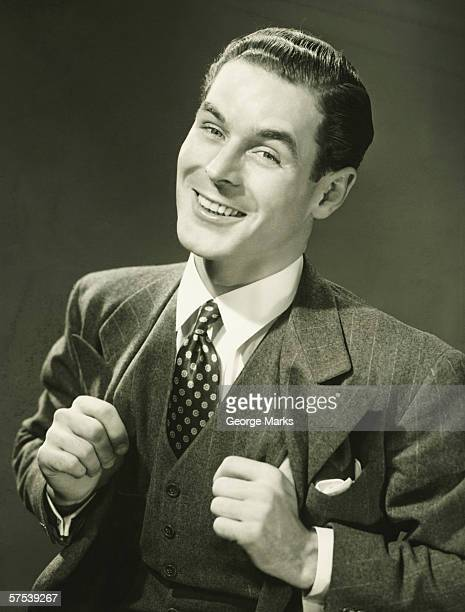 young businessman in studio smiling, (b&w), portrait - smug stock photos and pictures