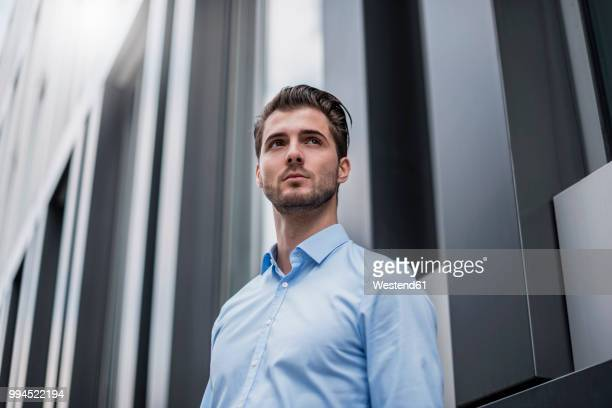 young businessman in the city outside office building - low angle view stock pictures, royalty-free photos & images