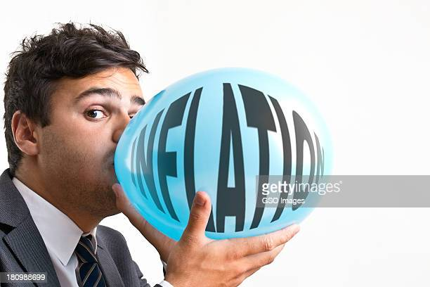 Young businessman inflating baloon