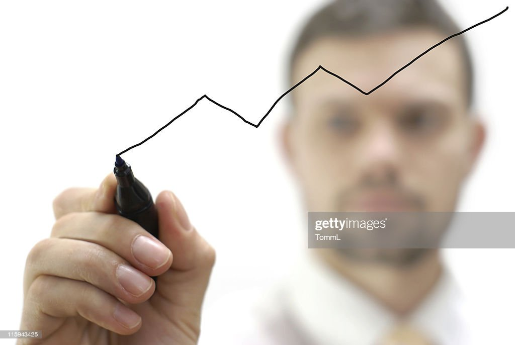 young businessman is drawing a decreasing graph / chart : Stock Photo