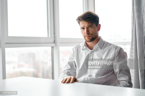 a young businessman is wearing a white shirt and is sitting at a white pillar next to a large window. - 白いシャツ ストックフォトと画像