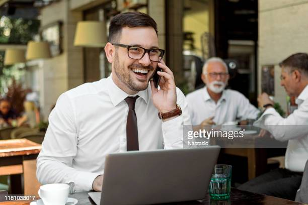 young businessman is working in a bar terrace with his laptop and smartphone - nomadic people stock pictures, royalty-free photos & images