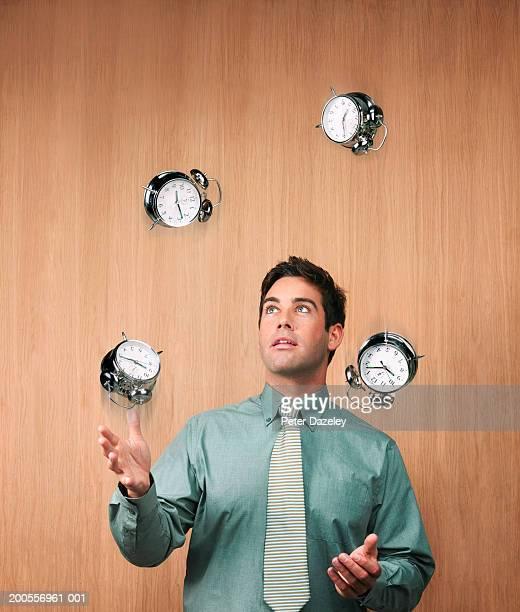Young businessman juggling alarm clocks, upper half