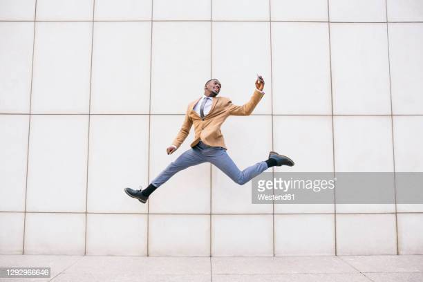 young businessman jumping and taking a selfie in front of a wall - menswear stock pictures, royalty-free photos & images