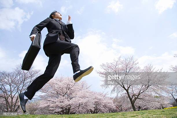 Young businessman jumping at the field of cherry blossoms, low angle view, Japan