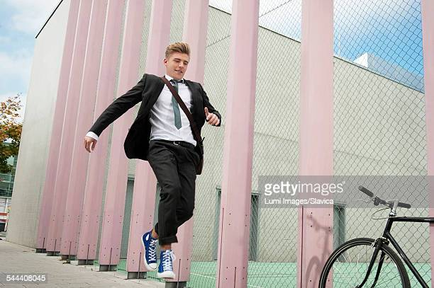 Young businessman jumping in air, Munich, Bavaria, Germany