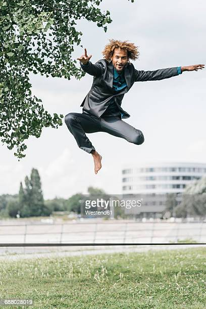 Young businessman jumping on slackline