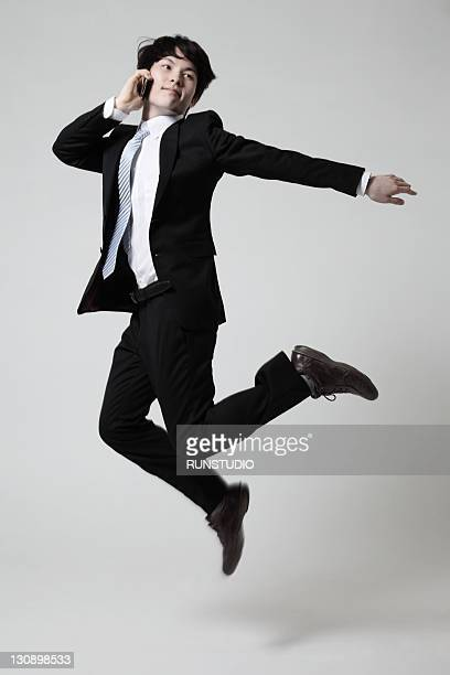 young businessman jumping with a mobile phone
