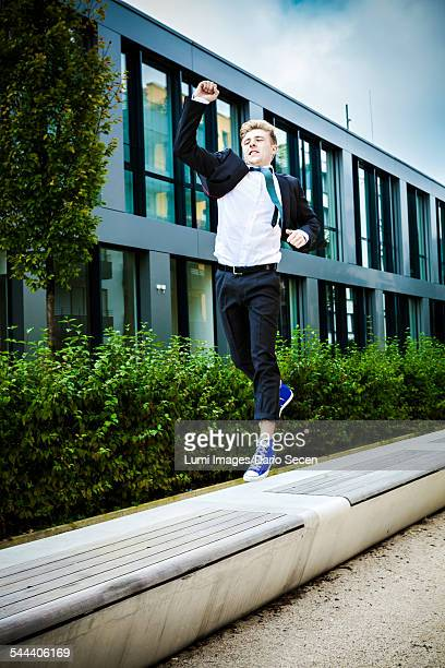 Young businessman jumps in air cheering, Munich, Bavaria, Germany