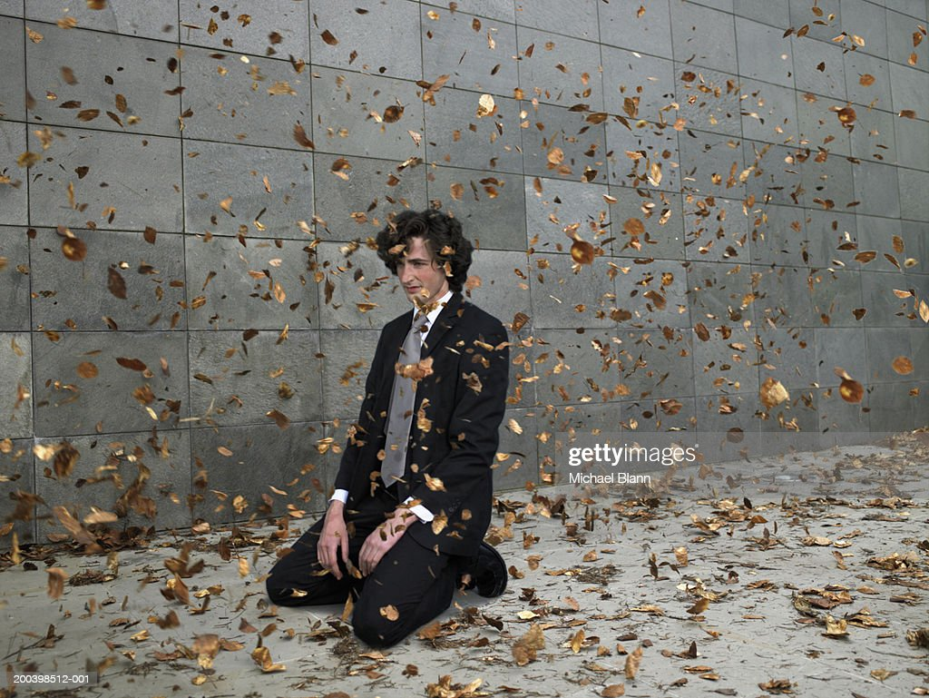 Young businessman kneeling on pavement amongst blowing leaves : Stock Photo