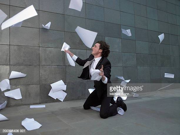 Young businessman kneeling on pavement, catching paper blowing in wind